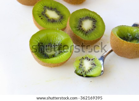 Fresh kiwis and a tea spoon on a white plastic cutting board.