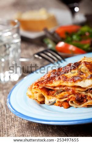fresh lasagna dish on a blue plate  - stock photo
