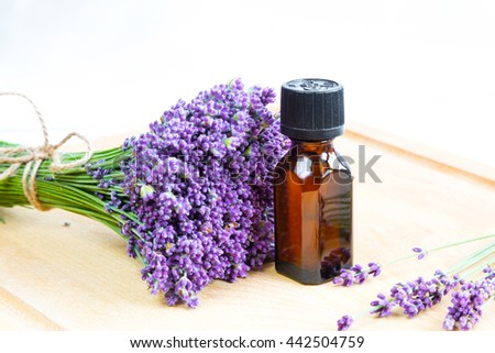 Fresh lavender flowers and bottle of oil on wooden background - stock photo