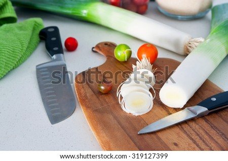 Fresh leek cut into rings with knife on wooden board in the kitchen, cherry tomatoes , kitchen towel and other utensil at background. Soft natural light, selective focus, main focus on the leek ring   - stock photo