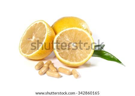 Fresh lemon and pills isolated on white, shallow focus - stock photo