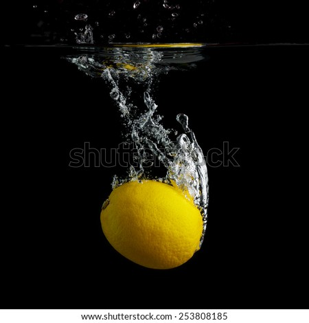 Fresh lemon falling into the water with a splash and air bubbles on black background. Wash fruits. - stock photo