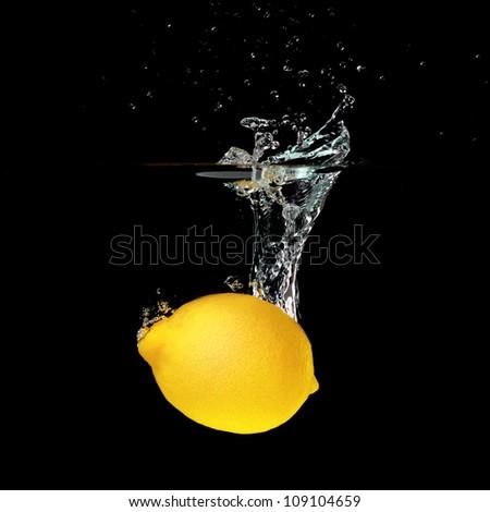 Fresh lemon falling into water isolated on black background - stock photo