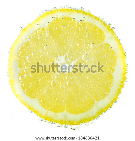 Fresh lemon in soda water covered with bubbles on white background - stock photo