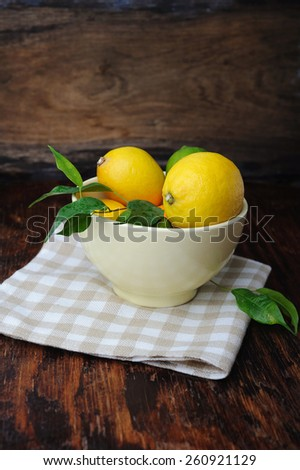 Fresh lemon in the bowl on wooden table - stock photo