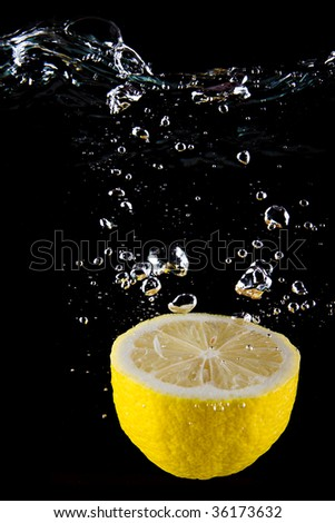 Fresh lemon  in the water isolated on black - stock photo