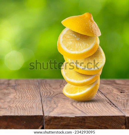 Fresh lemon slices on wooden table against green natural background - stock photo