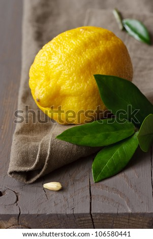 Fresh lemon with leaves on a linen napkin. - stock photo