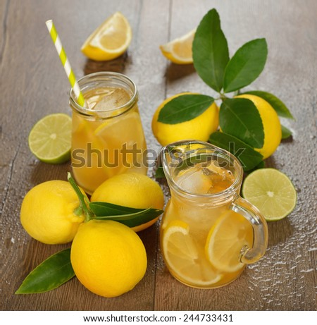 Fresh lemonade in a glass jug on a brown background - stock photo