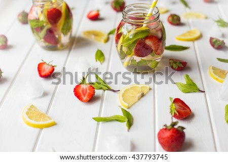 fresh lemonade with strawberries , lemon and mint on a wooden background - stock photo