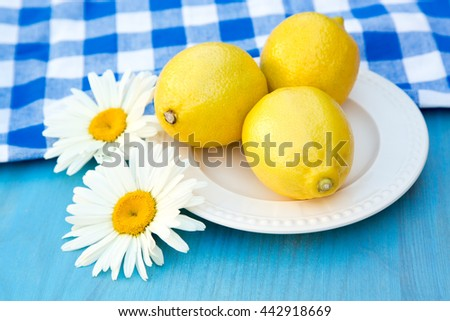 Fresh lemons and camomile on wooden table