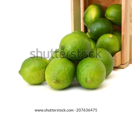 fresh lemons and lime fruits and some cut ones in a wooden crate on a white background  - stock photo
