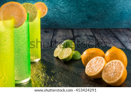 Fresh lemons and limes freshly cut with colored glasses - stock photo