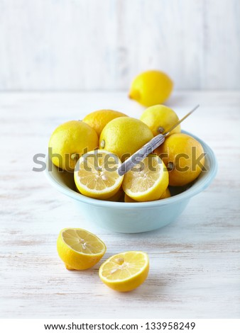 Fresh lemons in a bowl; whole and halved - stock photo