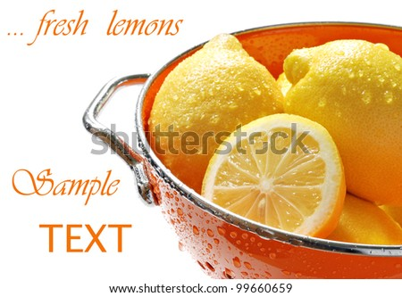 Fresh lemons in colorful orange colander with water droplets on white background with copy space.  Macro with shallow dof. - stock photo