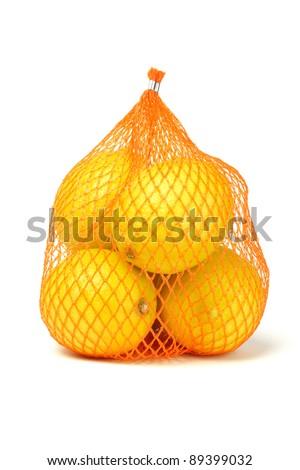 Fresh lemons in plastic netting sack on white background - stock photo