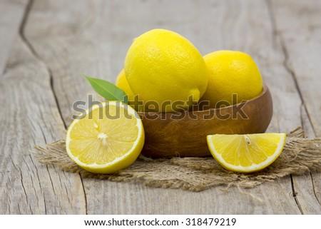 fresh lemons on wooden background - stock photo