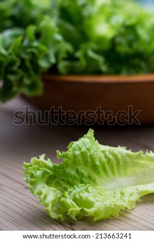 Fresh Lettuce, one leaf on wooden background, close-up, selective focus - stock photo