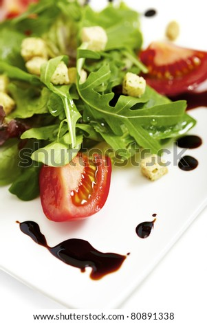 Fresh lettuce salad plate garnished with balsamic vinegar - stock photo