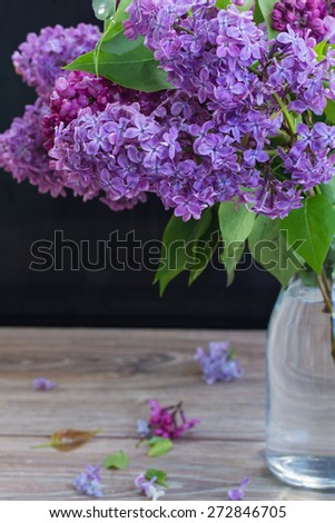 Fresh Lilac flowers  in glass vase on table - stock photo