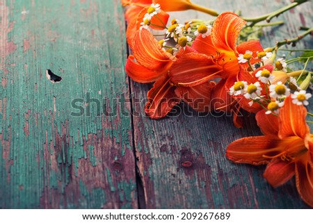 Fresh lily flowers on aged wooden board. - stock photo