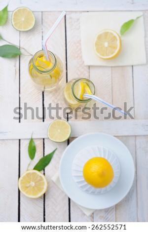 Fresh lime and lemon, squeezer and two glasses of lemonade on rustic table - stock photo