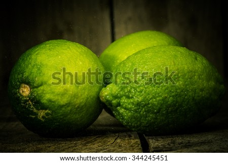 Fresh lime close up with drops of water on an old wooden table. - stock photo