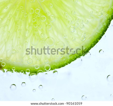 Fresh lime floating in frozen water - stock photo
