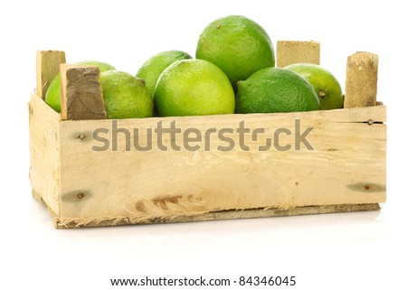 fresh lime fruit in a wooden crate on a white background