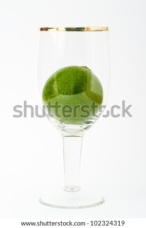 Fresh lime in glass cup isolated on white
