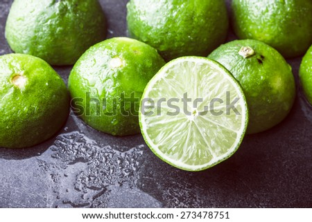Fresh limes cut in half on black surface - stock photo
