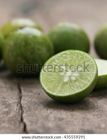 Fresh limes on old wooden table,close up. - stock photo