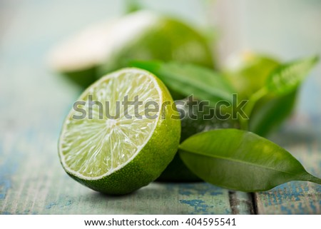 Fresh limes on wooden background, close-up. - stock photo