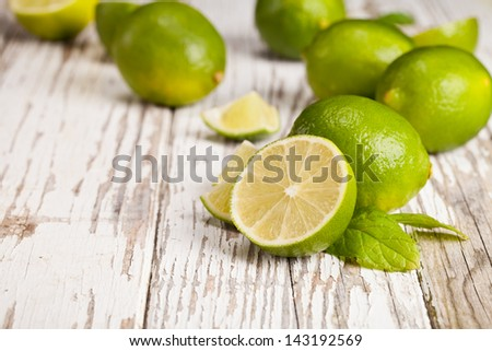 Fresh limes on wooden table - stock photo