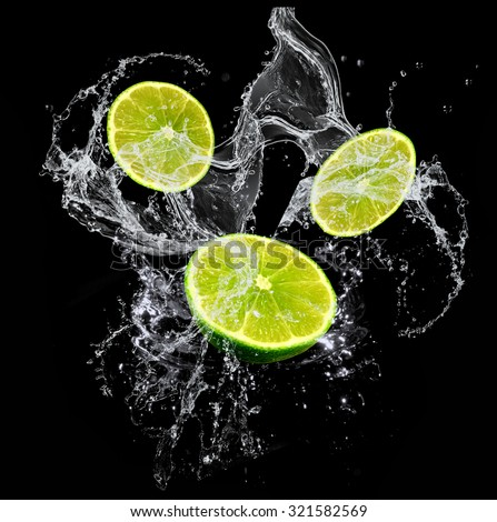 Fresh limes with a water splash isolated on a black background - stock photo