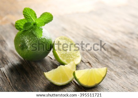 Fresh limes with mint, on wooden table - stock photo