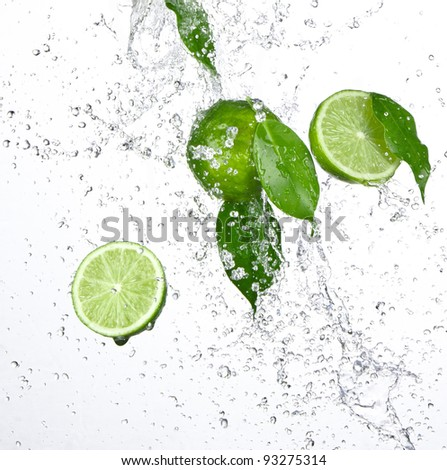 Fresh limes with water splash isolated on white - stock photo
