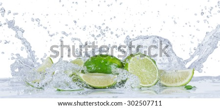 Fresh limes with water splashes - stock photo