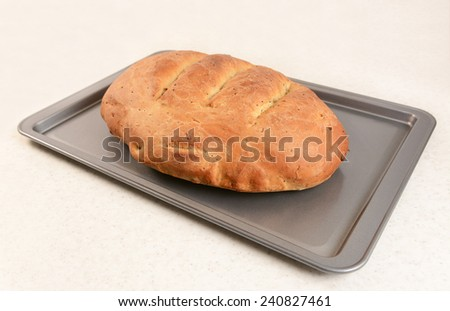 Fresh loaf of multi seed malted bread with slashed crust on a baking tray - stock photo
