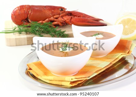fresh lobster soup with lemon, dill and cream dollop - stock photo