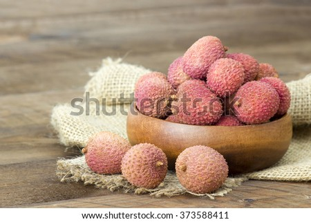 fresh lychees in a bowl  on wooden background - stock photo