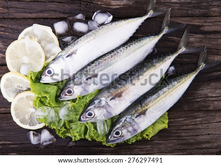 Fresh Mackeral on wooden background with lemon - stock photo