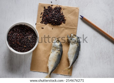 Fresh mackerel or tuna steamed fish with riceberry on vintage white table and paper for notes - stock photo