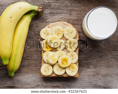 Fresh made banana bread and milk  on old wooden table - stock photo