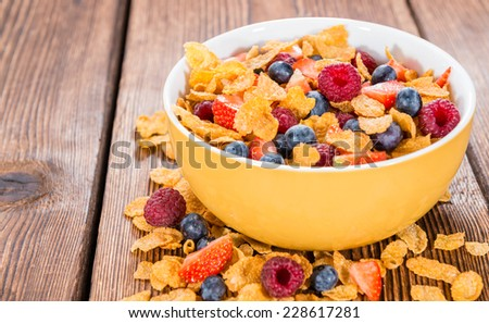 Fresh made Breakfast (Cornflakes with different Berries) on wooden background - stock photo