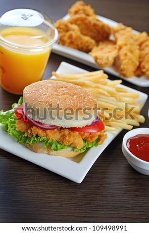 Fresh made burger with fries and crispy chicken. - stock photo