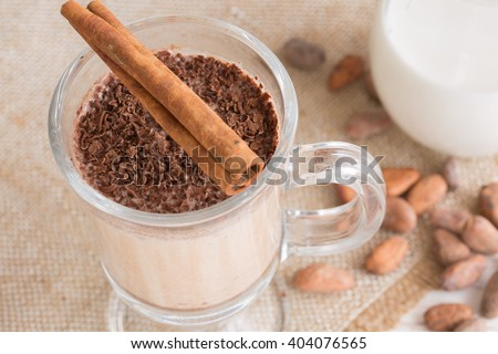 Fresh Made Chocolate Banana Smoothie on a wooden table with coffee and spices. Milkshake. Protein diet. Healthy food concept. Drink, cocoa beans, chocolate. - stock photo