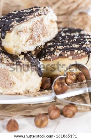 Fresh made filled Hazelnut Donuts on vintage background - stock photo