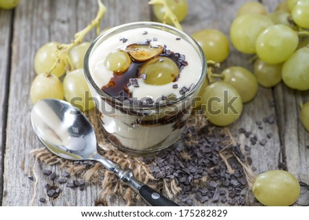 Fresh made Grape Yogurt with Chocolate Sauce on vintage wooden background - stock photo
