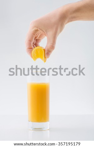Fresh-made juice. Human hand squeezing a piece of orange to make fresh juice.